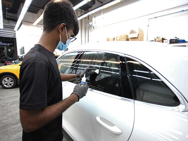 A Man Appying DFI Windows Coating to a Car | Lambency Detailing